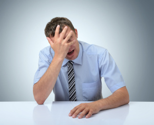 Businessman do a facepalm on white table